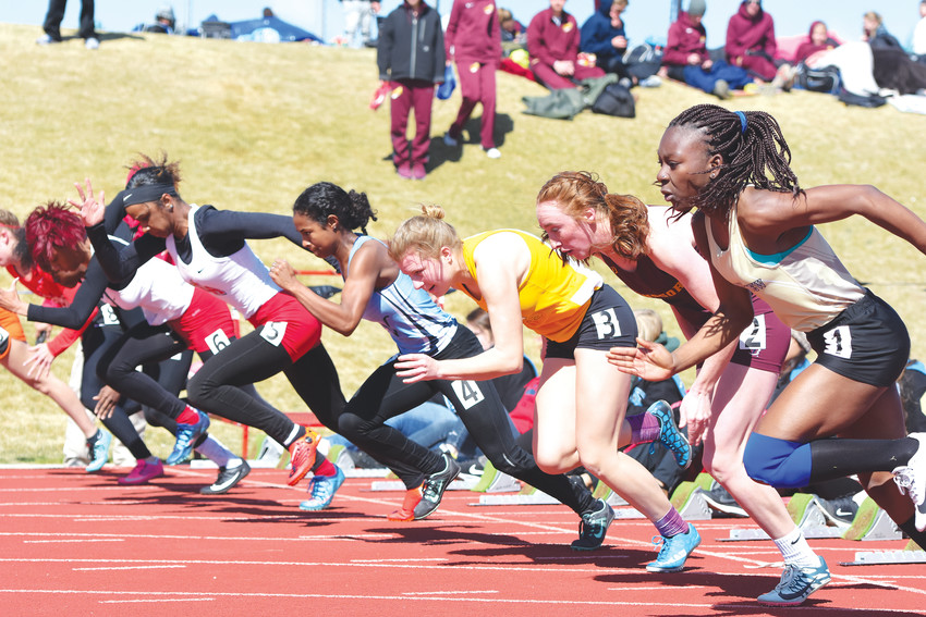 A group of girls sprinters depart the starting blocks during one of several 100-meter dash heats at the Mountain Range Invitational Track and Field Meet on April 14 at Adams 12 North Stadium in Westminster. Strong winds would disallow any state meet qualifications made during the competition.
