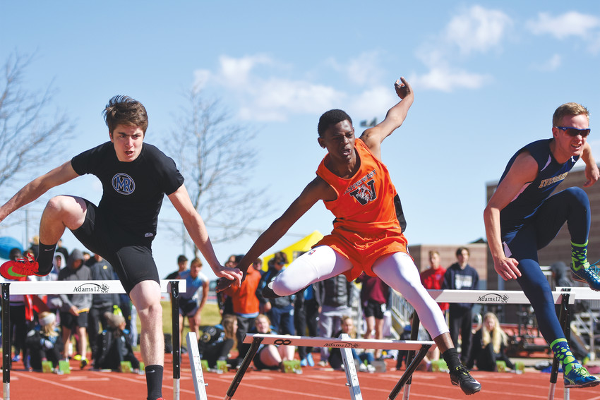 Zach Weiss of Mountain Range, left, Julius Cotton, center, of Denver West, and Carter Hudson, of Evergreen, compete in a 110-meter intermediate hurdle heat at the Mountain Range Invitational Track and Field Meet on April 14 at District 12 North Stadium in Westminster.