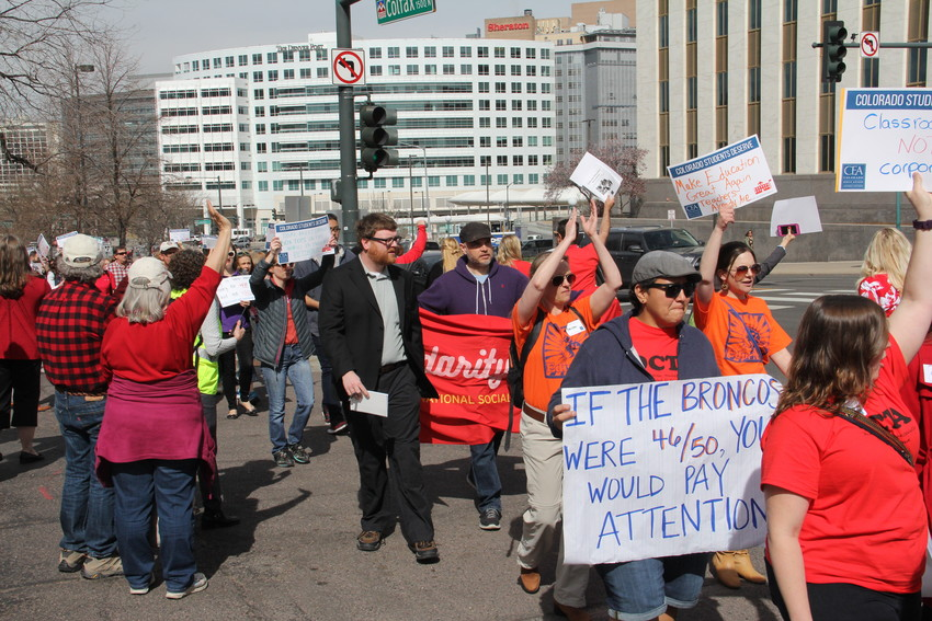 "Teachers and other educators march on the April 16 ""Day of Action,"" where about 400 protested some changes to the state's public-pension system and advocated for more school funding at the Capitol. The sign at bottom right references a 2016 ranking of Colorado's average teacher pay as 46th in the nation by the National Education Association. That figure was revised in updated NEA rankings to 31st in average teacher pay in 2017 and 30th in 2016."