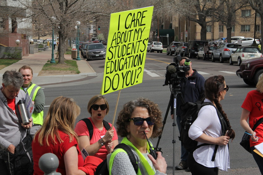"Kathryn Brown, a counselor at Colorado's Finest High School of Choice in Englewood, holds up a sign at the April 16 ""Day of Action"" organized by the Colorado Education Association. Brown was among about 150 educators from Englewood who planned to come to the event — more than 70 percent of Englewood's teacher workforce planned to be absent April 16."