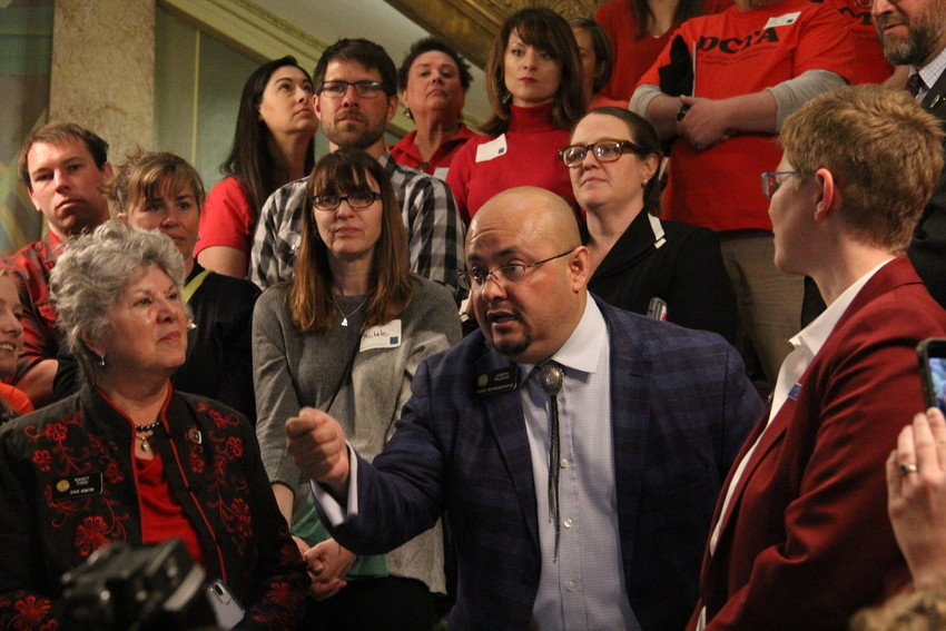 State Rep. Joe Salazar, D-Thornton, speaks to the crowd of educators at the state Capitol April 16. Sen. Nancy Todd, D-Aurora, left in black and red; and state Rep. Daneya Esgar, D-Pueblo, above in black, flanked Salazar.