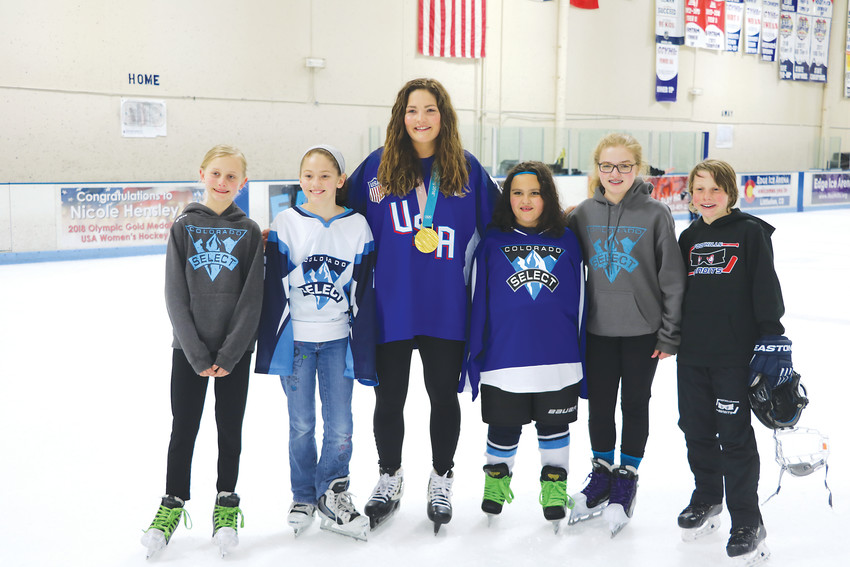 Nicole Hensley, a goalie who won gold at this year's Olympics, poses with goalies from the local Foothill Fliers and Colorado Select hockey teams at Littleton's Edge Ice Arena on April 15.