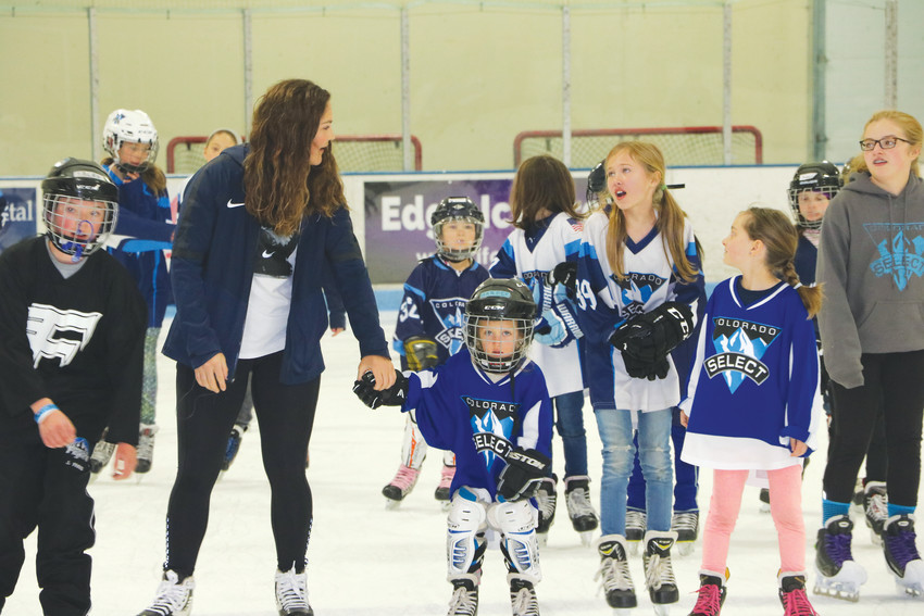 Gold-medal winner Nicole Hensley skates with Foothills Fliers and Colorado Select players on April 15 at the Edge Ice Arena.