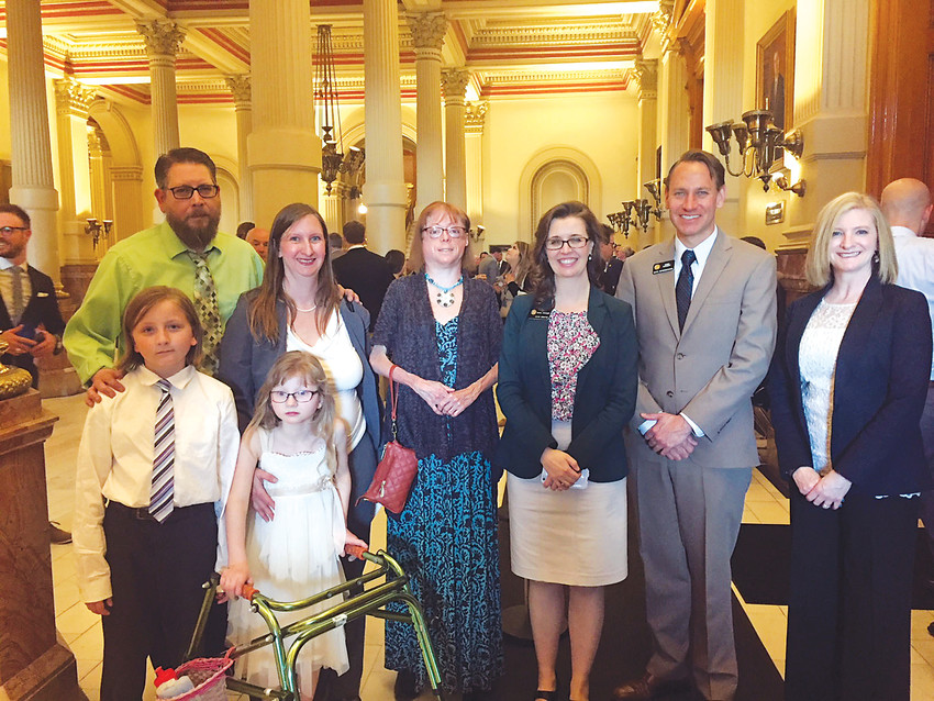 Chad and Susan Hoyt and their children Jackson and Grace, Joan LaBelle, Sen. Rachel Zenzinger, Rep. Chris Kennedy and Dr. Wendi Drummond pose for a photo after Gracie's Bill was signed into law April 2.