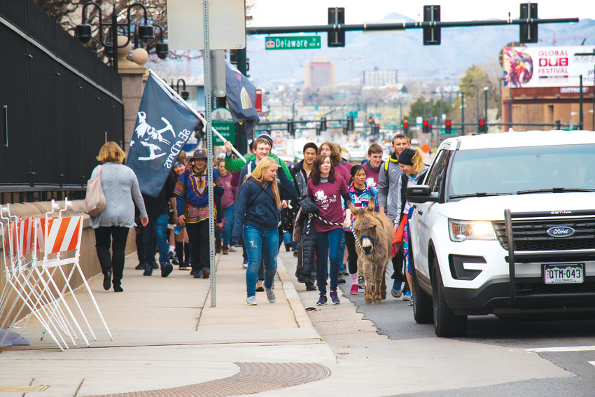 Colorado School of Mines students make their way east along Colfax Avenue on April 13, led by Blaster the school mascot, for the annual Ore Cart Pull walk to the capitol building. The march from Golden to Civic Center Park in Denver is a school tradition.