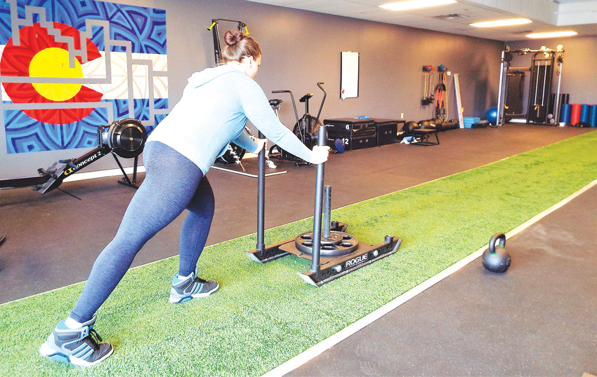 Trainer and Empire Fitness co-founder Amanda Weber pushes a weight sled inside her Westminster studio.
