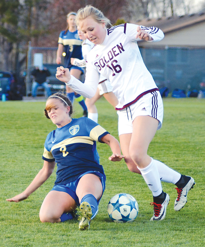 Wheat Ridge senior Eryn Dominguez (2) slides in an attempt to steal the ball from Golden junior Grace Guerra (16) during a Class 4A Jeffco League game April 18 at Lakewood Memorial Field. The Farmers ended a 2-game conference losing streak with a 4-1 victory over the rival Demons.