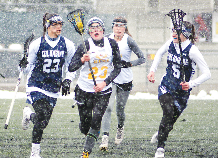 Green Mountain senior Samantha Day (23) followed by teammate Sara Haefele race down the field while being flanked by Columbine juniors Whitney Block (23) and Emma Maxwell (5) on April 21 at Trailblazer Stadium. The Rams and Rebels played in the Jeffco League game in a snowstorm. Columbine came away with a 19-4 victory.