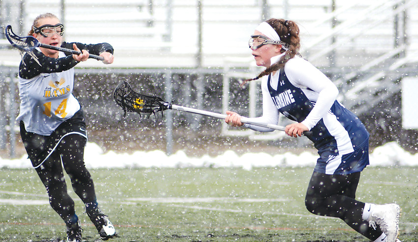 Green Mountain junior Rachel Bales (14) attempts to cut off the path of Columbine senior Jazlyn Flores to the goal during a snowstorm April 21 at Trailblazer Stadium. The Rams couldn't upset Columbine as the Rebels took a 19-4 victory.