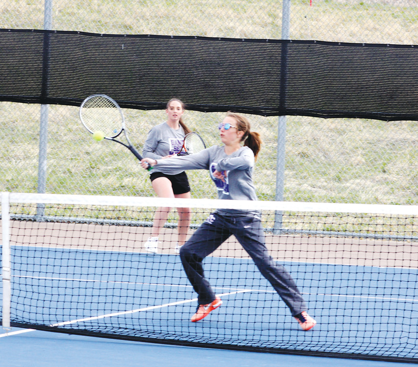 Douglas County's Jordan Abdo hits a forehand volley at the net as her partner Abby King watches during their No. 2 doubles match on a cold, windy April 19 afternoon during a dual girls tennis match at Legend. Abdo and King were undefeated in six matches but Abby Fields and Becky Schamp of Legend notched a 1-6, 7-6 (7-5), 10-8 victory to hand the Huskies' doubles team its first loss of the season. Legend earned a 5-2 team victory.