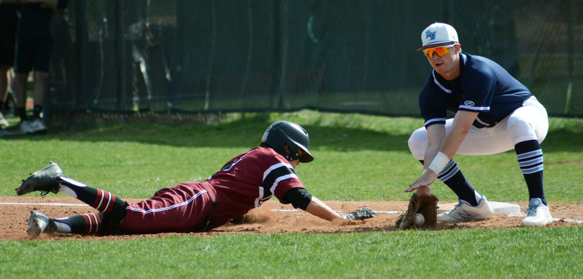 Ralston Valley sophomore Billy Wall, right, puts down a tag as Chatfield junior Sam Low slides back to first base during the Class 5A Jeffco League game Monday, April 23, at Chatfield Senior High School. The Mustangs suffered a 9-7 loss.