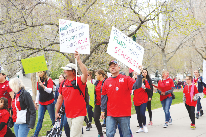 Wearing red, educators from Douglas County held up powerful signs as they marched alongside the state Capitol at a rally on April 26. Participants were calling for additional funding for public schools.