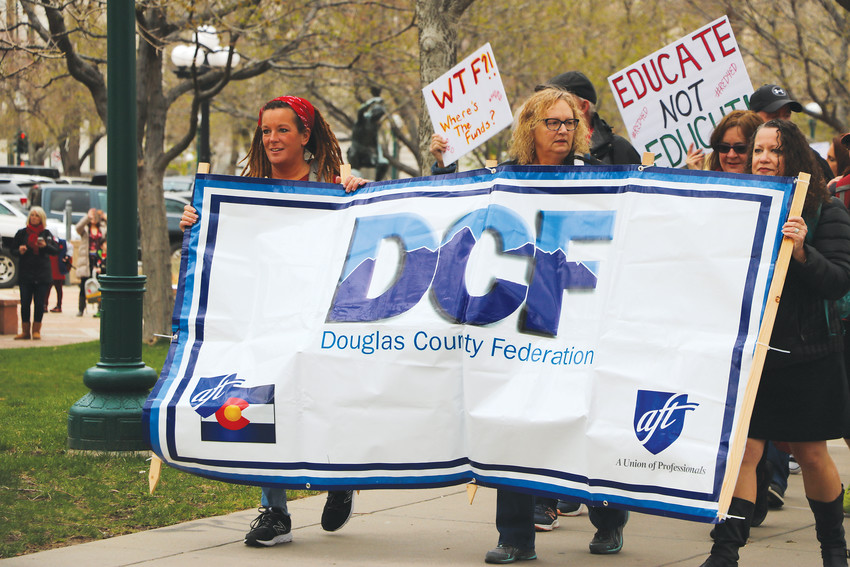 Members of the Douglas County Federation, the local teachers union, march alongside the state Capitol at a rally on April 26. They were protesting for additional funding from the state for public education.