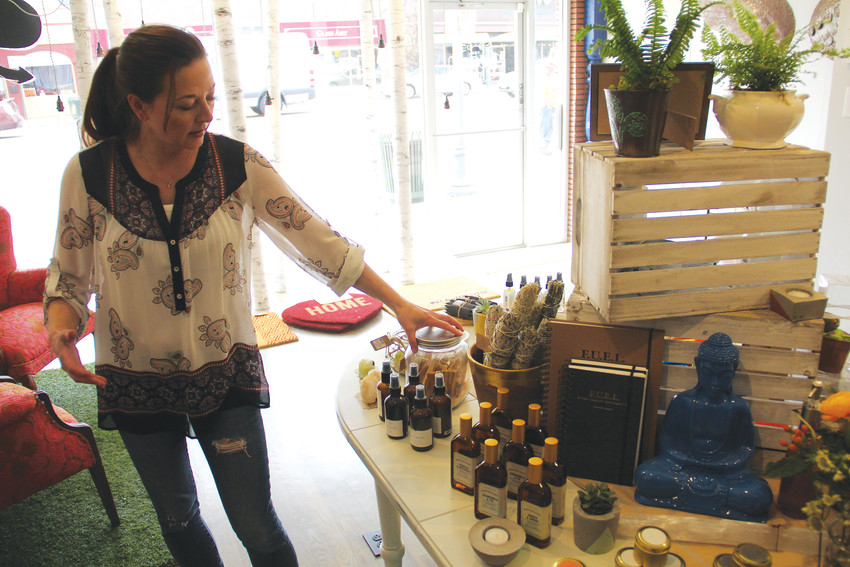Carrie Moore, owner at the Peace Cellar in downtown Englewood, talks about products at the front of the store April 10. Peace Cellar sells apothecary products, kombucha, plants, clothing, crystals, art, gifts and more.