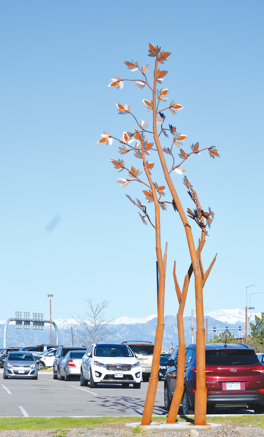 "A view of one of four multi-colored metal and glass seeds from the sculpture ""Native Grasses"" by artist C.J Rench at Webster Lake Promenade, off of 120th Avenue and Grant. The piece was commissioned by the Northglenn Arts District expressly for the center of the shopping center's parking lot."
