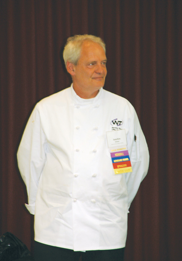 Chef Joachim Schaaf stands awaiting his award at the 28th annual Good News Breakfast. Schaaf received the honor for his efforts of empowering Jeffco high schoolers and adults to pursue careers in culinary arts.