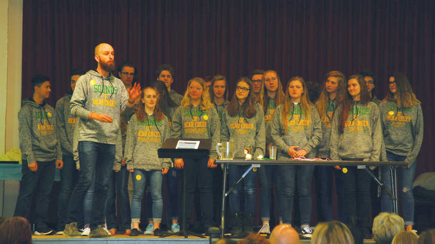 Director Duncan Cooper, front, introduces the student singing group, the Sounds of Bear Creek of Bear Creek High School as the musical performers at the 28th annual Good News Breakfast on April 24.