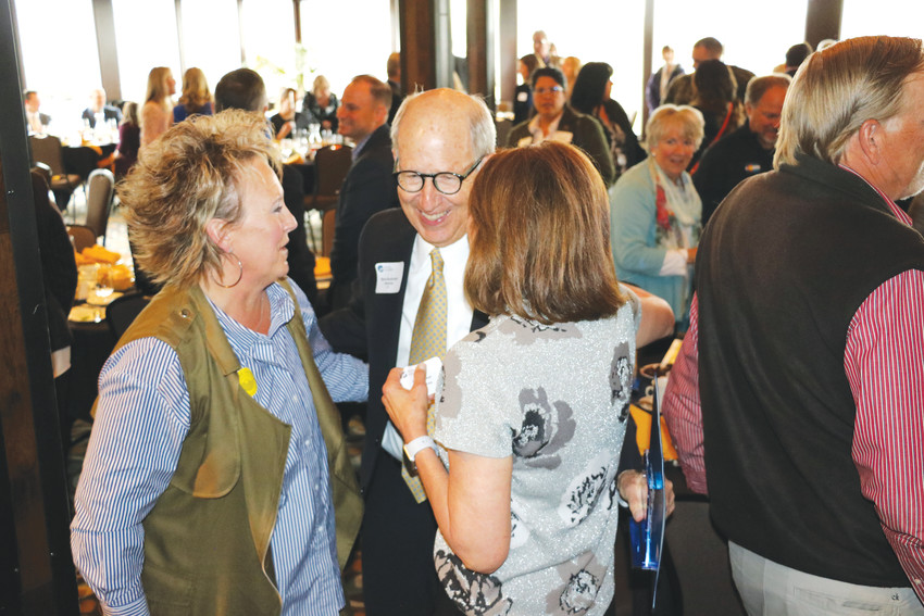 Hall of Fame inductee Steve Burkholder visits with friends following his induction into the West Metro Chamber's hall of fame on April 24 at Applewood Golf Course.