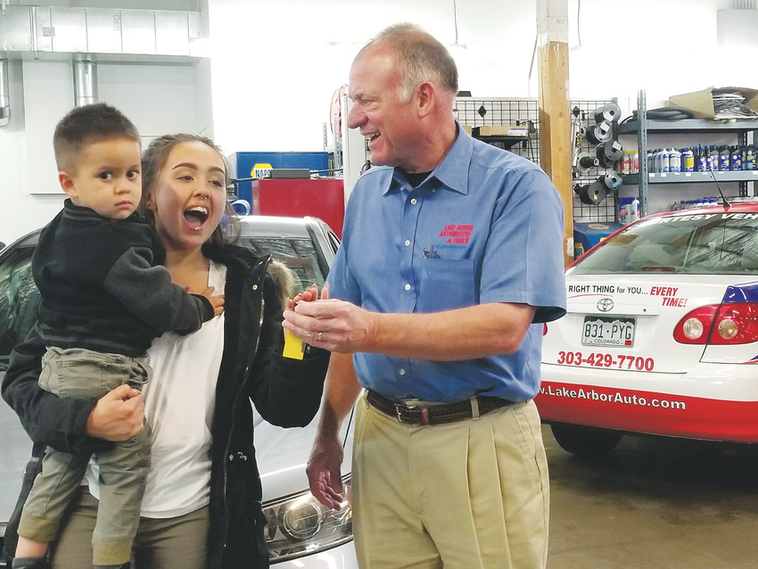Dana TePoel, owner of Lake Arbor Auto, presents the keys to a donated car to teen mom J.C. Magalso, 19, and her son is Aivenn, 2.