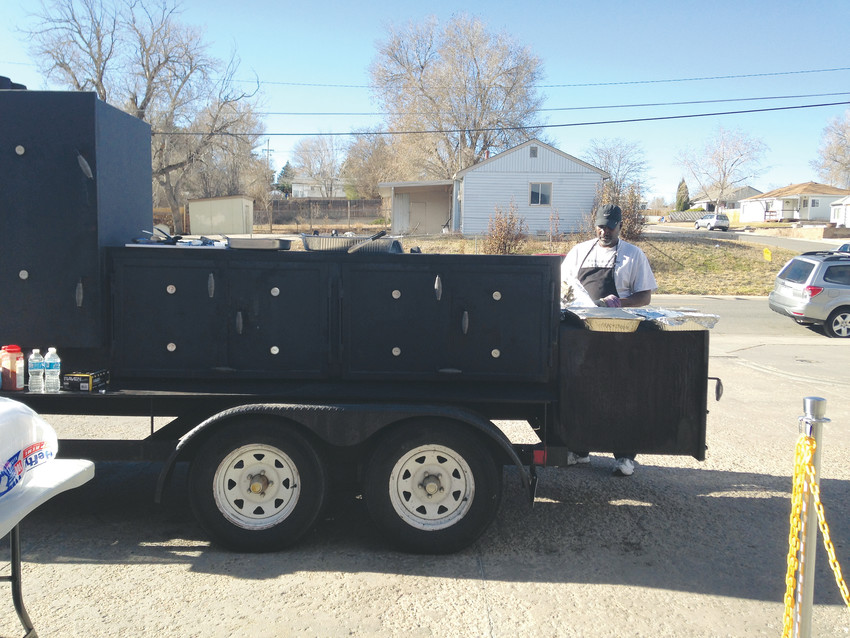 Bruce Washington tends one of the two trailers he uses to smoke his meats for Taste of Texas BBQ.