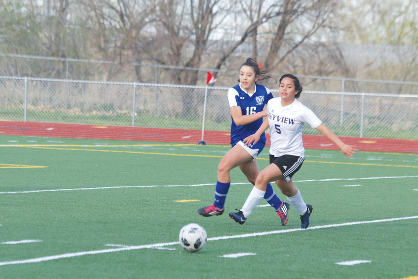 Sophomore Alyssa Escalacra, 5, works to gain control of the ball for Skyview and keep it away from her Englewood opponent during the May 1 league girls soccer game. Eacalacra got control of the ball and helped the Wolverines continue their attack that scored a goal as Skyview won the game, 11-1.