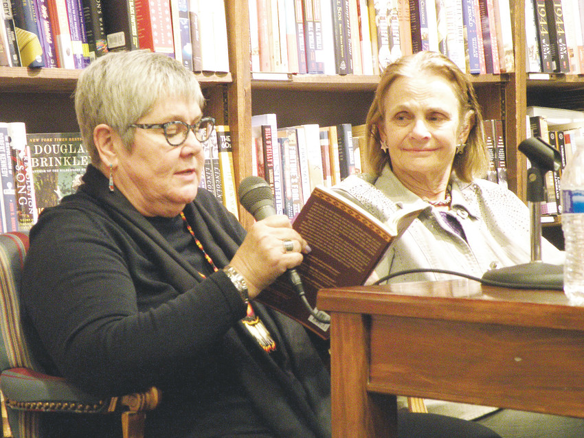 "Sara Sue Hoklotubbe, left, reads from her new novel ""Betrayal at the Buffalo Ranch,"" while fellow novelist Anne Hillerman, author of ""Cave of Bones,"" looks on. The two western mystery authors appeared together at the Tattered Cover on May 3 to discuss life and the craft of writing."