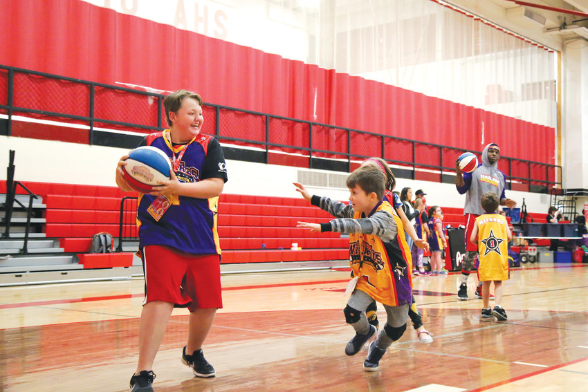 "Hunter Lee, 12, plays basketball with other ""Wiz Kids"" before the game begins."