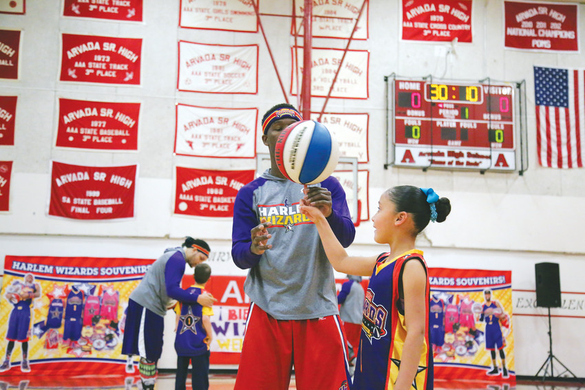 Averiella Domenech, 7, spins the basketball with the help of a Harlem Wizard basket player before the big game May 4.