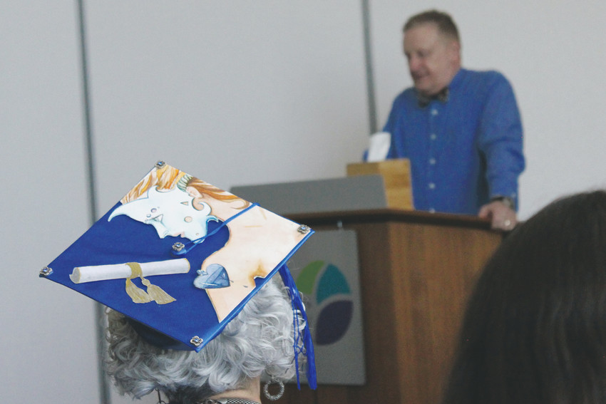 Douglas County High School Equivalency graduates listen to Ian Stanford, community educational outreach instructor, during the program's first graduation ceremony May 6. One graduate got creative with her cap.