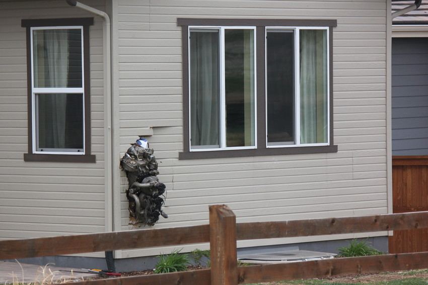 The engine of an SR22 plane that crashed around 8:30 May 11 was propelled several hundred yards and embedded into a home nearby the crash site, just west of the Stepping Stone neighborhood. Photo by Tabatha Stewart