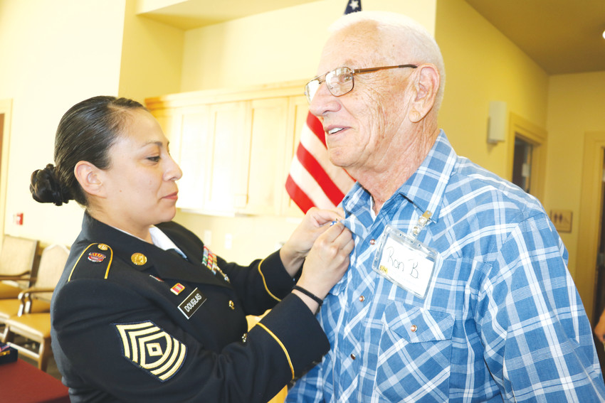 US Army Corporal Roland Baldwin receives a pin from 1st Sgt. Margarita Douglas at an early Memorial Day ceremony at the Senior Resource Center on May 11.