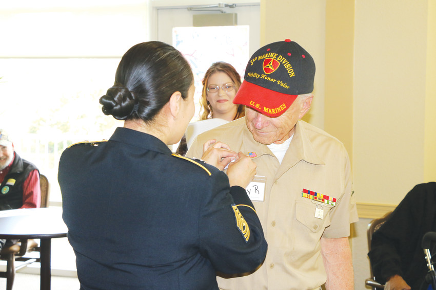 Marine Corp Private First Class Gary Raymer receives a pin from 1st Sgt. Margarita Douglas at an early Memorial Day ceremony at the Senior Resource Center on May 11. Raymer was one of about 25 veterans celebrated at the center for early Memorial Day.