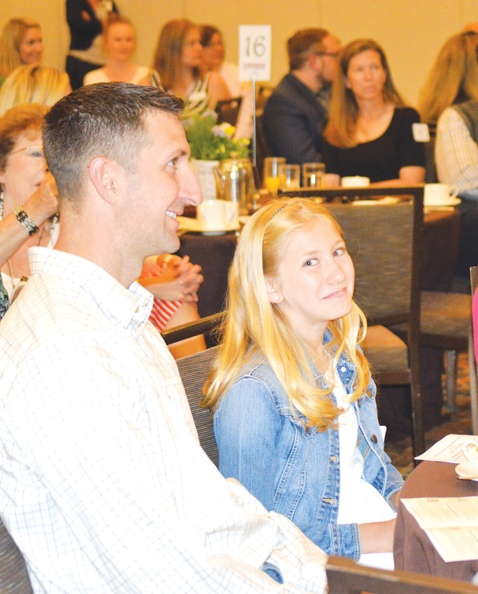 Arapahoe Ridge Fifth grader Addison Ginther, alongside her father Luke, reacts as she is named the Citizen of the Year at the Westminster Legacy Foundation's Community Award breakfast. Ginther won the title for her volunteer work.