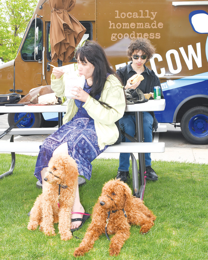 Leilani May and son Brandon, 17, of Westminster, sample some of the fare at this year's Northglenn Food Truck Carnival, as their newly acquired standard poodle pups, Jaster, right, and Rosie learn social skills May 11 at the Northglenn Community Center. The dogs are 15 weeks old.