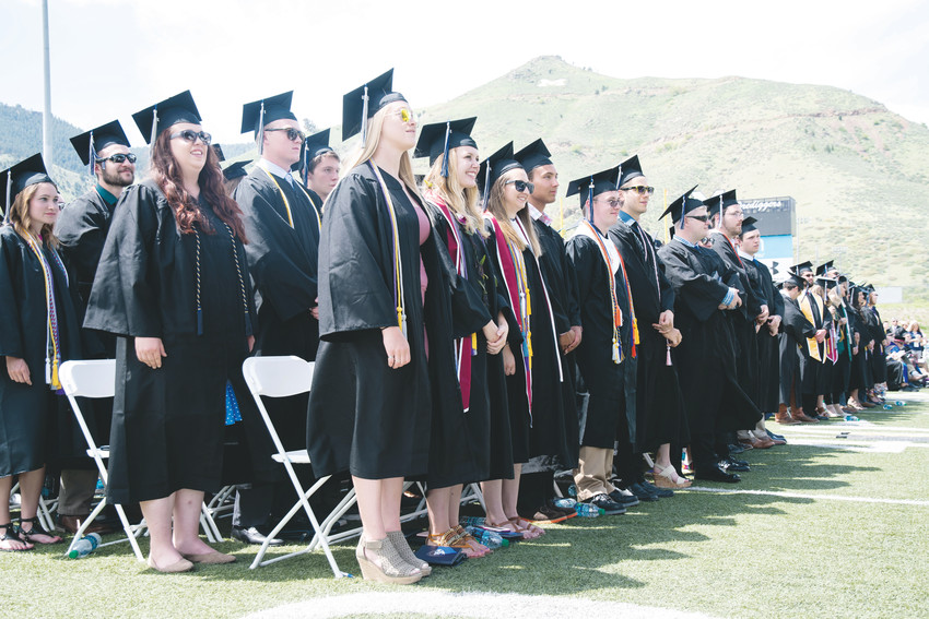 Colorado School of Mines undergraduate students stand in recognition of their achievements at their commencement ceremony on May 11 at Marv Kay Stadium on Mines campus in Golden.