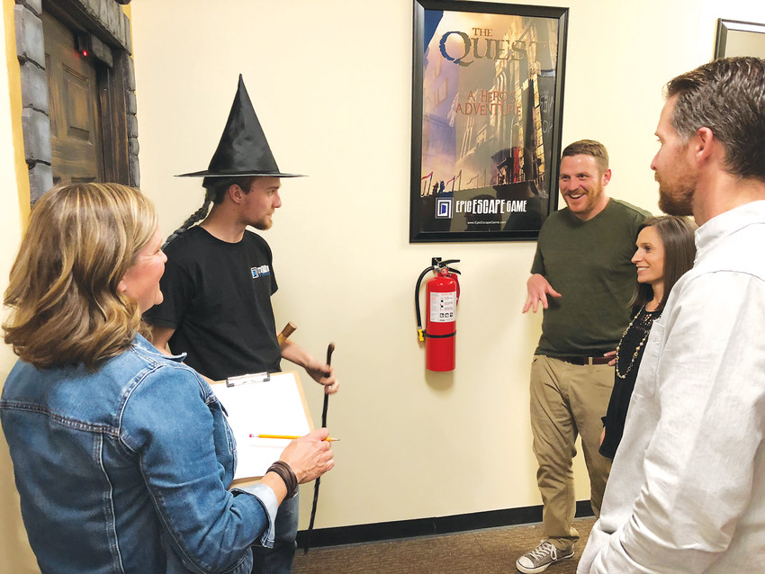 "Lucas Wojtalewicz, pictured in the wizard hat, leads a group through the introduction to ""The Quest,"" one of five games available at the Epic Escape Game."