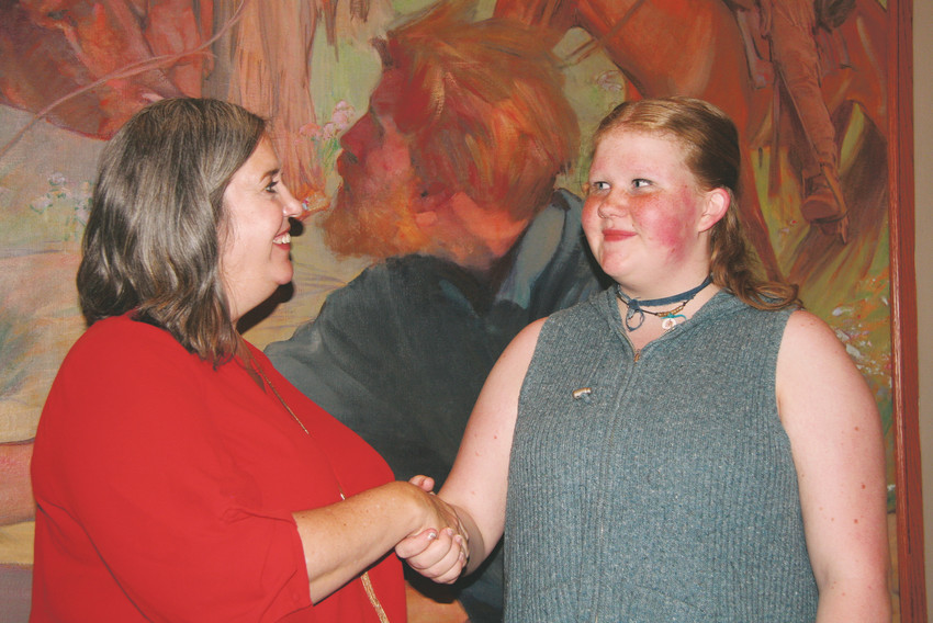 Jody Thomas, left, one of the contests' judges, shakes hands with Seyennah Rae, a ninth grader at Sobesky Academy in Wheat Ridge, and congratulates her on her third-place win in the Education Nonprofit Corporation's Jeffco Writing Challenge.