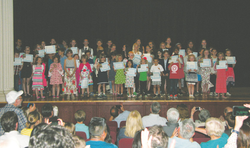 Parents of the winners of the Education Nonprofit Corporation's Jeffco Writing Challenge and I Love to Read Contest take their children's pictures in a group photo op at the awards ceremony May 11 at the American Mountaineering Center in Golden.