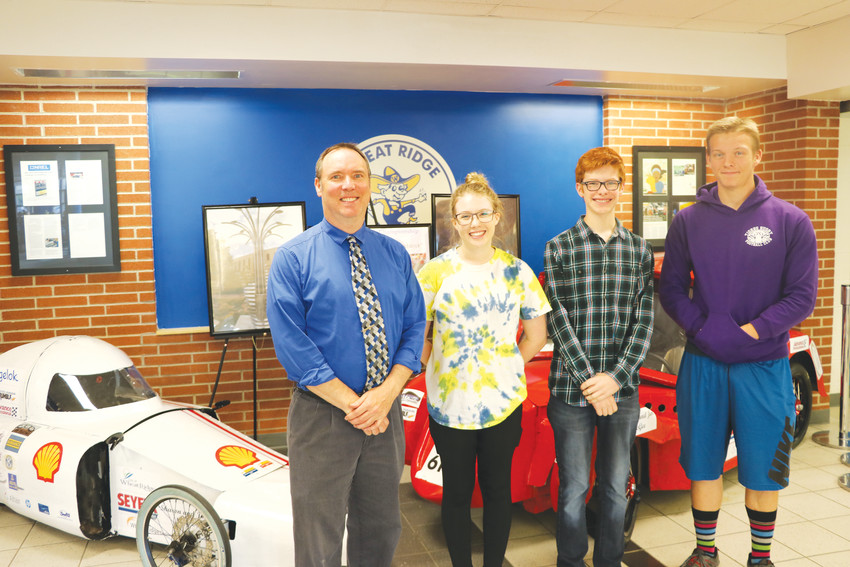Wheat Ridge High School's STEM instructor Chuck Sprague and students Ali Helton, Isaac Fernald and Connor Denny in front of the two cars they entered in this year's Shell Eco-Marathon.