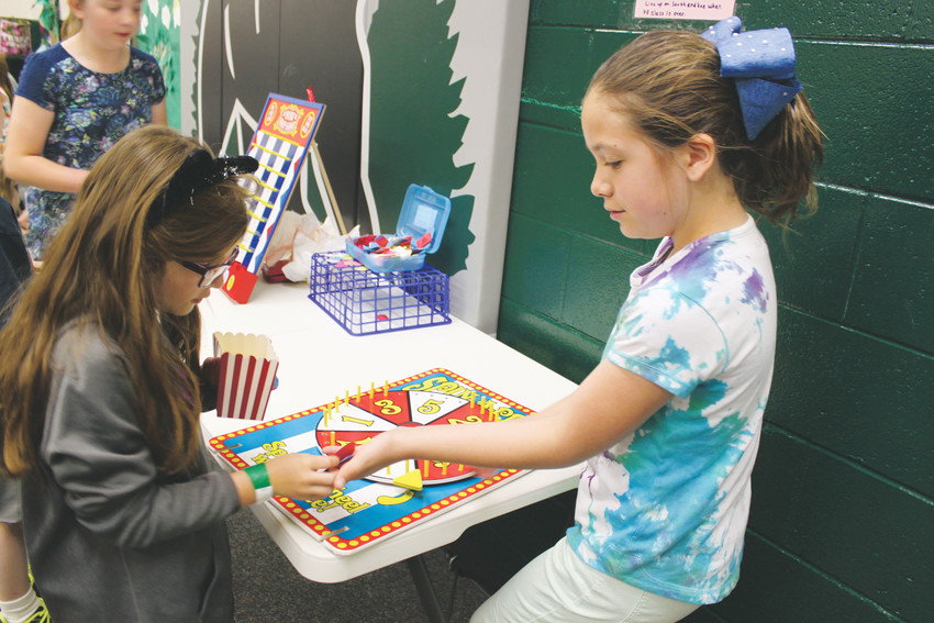 Mia Roth, 10, helps fellow Pine Lane students play Spin The Wheel during the school's student-driven fundraiser to raise money to help save the Amazon rainforest.