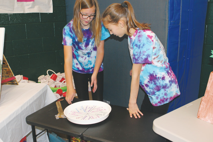 Pine Lane students Devin Ewald, 11, and Maddie Romero, 11, prepare their Forest Fade and Prize Punch games during the school's fundraising carnival.