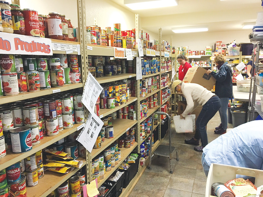 Volunteers shelve food at the Christian Action Guild's food pantry in Golden. The nonprofit organization benefitted from the 26th annual Letter Carriers' Stamp Out Hunger Food Drive.
