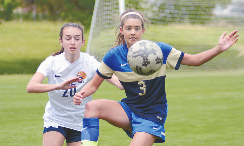 Wheat Ridge senior Macie Browne (3) attempts to settle the ball in front of Evergreen sophomore Sofie Cochran during the Class 4A girls soccer state tournament second-round game May 12 at Lakewood Memorial Field.