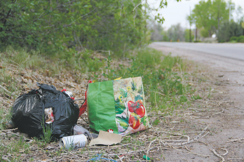 A tote bag of cans, plates and food containers next to a garbage bag of other materials and a beer can along South Platte River Drive in Englewood May 6. Personnel from the City of Englewood, outside homeless-resource volunteers and other governmental agencies carried out a cleanup of the river in January, during which 21 camps were located and about 25 truckloads of trash were removed from along the river.