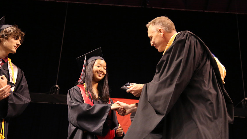 Pomona Principal Andy Geise congratulates Jing-Mei Fillmore, one of the Class of 2018's valedictorians. She shares the honor with her sister, Xuedan.