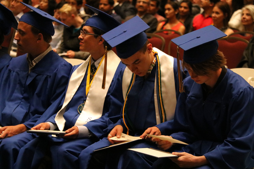 Graduates of STEM School Highlands Ranch inspect their newly-acquired high school diplomas at a May 18 commencement ceremony at University of Colorado South Denver in Parker.