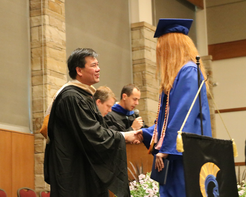 Douglas County School Board member Kevin Leung congratulates a graduate of STEM School Highlands Ranch at the May 18 commencement ceremony in Parker.