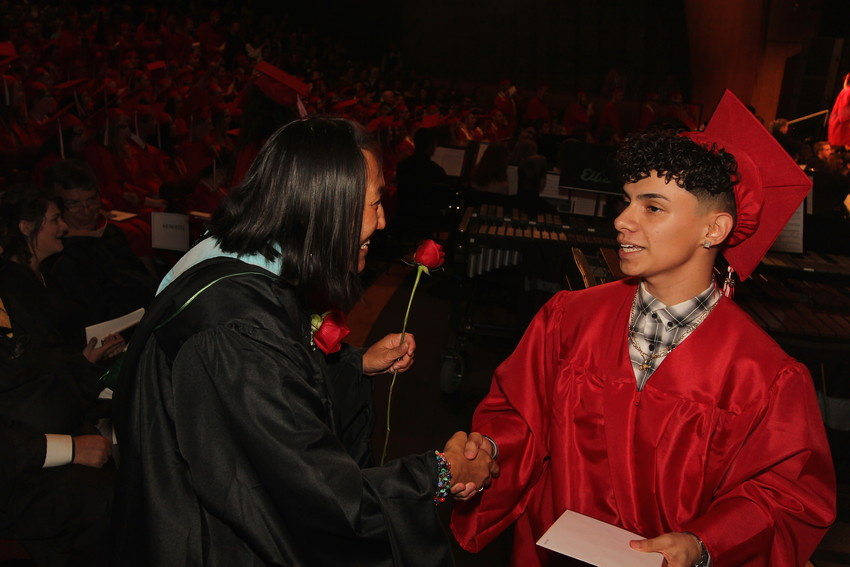 A student talks with a faculty member at the Arvada High School Class of 2018 graduation.