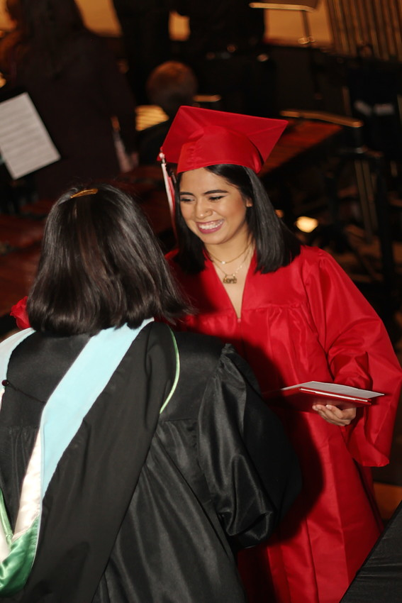A student accepts her diploma as an Arvada High School graduate.
