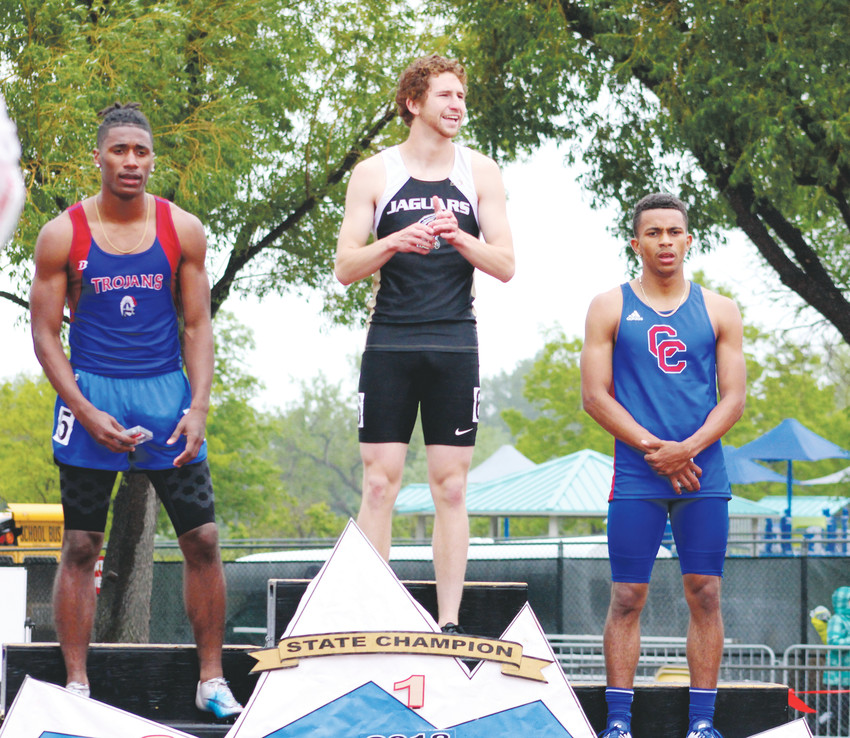 Class 5A 100-meter champion Devin Cadena of Rock Canyon is flanked by Cherry Creek's third-place finisher Marcus Miller, right, and second-place finisher Deondre Ritter of Fountain Fort Carson.